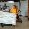 Jeff Funk (left) hands the One Grand Crazy Summer Giveaway $1,000 check to Peggy Base (center), from Enid, at Oakwood Mall Saturday, July 26, 2014. Base, who shops at Jumbos, was excited about her win, sponsored by Communication Federal Credit Union. Ginger Cass (right) won the trip to Branson, sponsored by Enid Travel Consultants. (Staff Photo by BONNIE VCULEK)