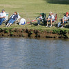 Fishing enthusiasts relax on the bank at Meadowlake Park as they vie for tagged fish during the annual Fourth of July fishing derby Friday, July 4, 2014. (Staff Photo by BONNIE VCULEK)