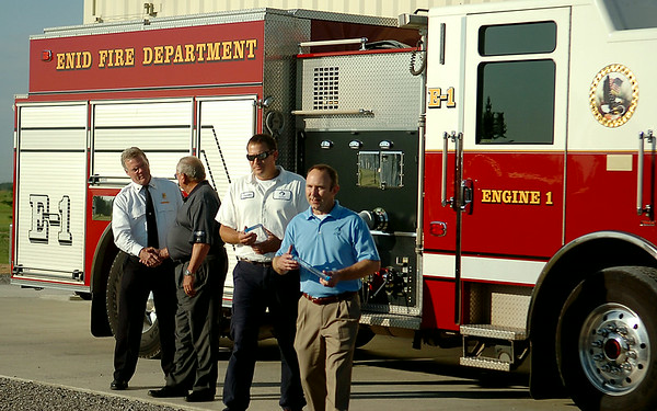 Enid Fire Chief Joe Jackson (left) and Autry Technology Center Superintendent Dr. James Strate shake hands during the ribbon cutting ceremony for the new Fire Training Tower at Autry Technology Center Tuesday, July 29, 2014. (Staff Photo by BONNIE VCULEK)