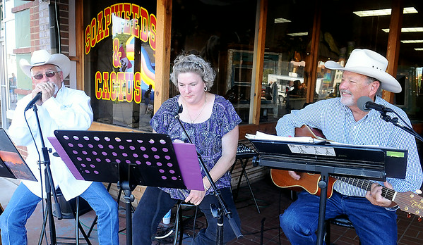 """Back Home Again"" performs outside Soapweeds & Cactus during Main Street Enid's Second First Friday in downtown Enid July 11, 2014. (Staff Photo by BONNIE VCULEK)"