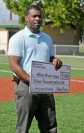 Brandon Morris (left), the director of public affairs for Union Pacific Railroad in Oklahoma and Arkansas, pauses on the artificial turf at AMBUCS ABC Park before presenting a $15,000 donation to the 4RKids Miracle League Wednesday, July 9, 2014. The funds will help complete additional renovations at the park. (Staff Photo by BONNIE VCULEK)