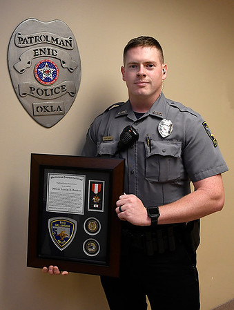 Officer Austin Burkes holds a life saving award from the Enid Police Department. (Billy Hefton / Enid News & Eagle)