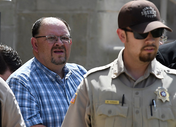 Garfield County sheriff, Jerry Niles, is led from the Garfield County Courthouse Tuesday July 25, 2017 after being indicted on felony second degree manslaughter in the death of an inmate at the Garfield County detention center last year. (Billy Hefton / Enid News & Eagle)