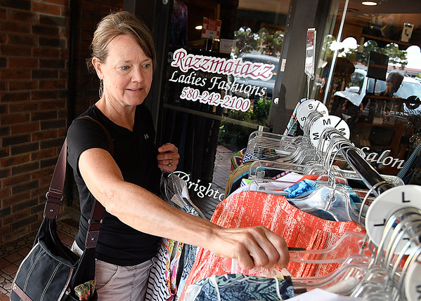 Shannon Cowman looks through a rack of sale items at Razzmatazz during the Crazy Days sale Saturday July 29, 2017. (Billy Hefton / Enid News & Eagle)