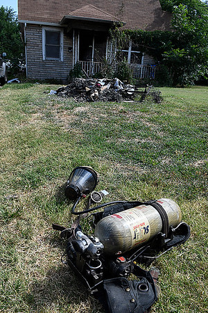 Firefighting equipment and debris lay in the yard of a house at 205 E Hickory after a fire Saturday July 1, 2017. (Billy Hefton / Enid News & Eagle)