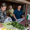 Jana Terrell (left), Sherry Koehn (back) and Anna Friesen (right) work the K & S Produce stand east on Ringwood Wednesday July 25, 2018. (Billy Hefton / Enid News & Eagle)