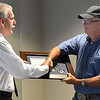 Sgt. Quent Tubbs (right) shakes hands with police chief Brian O'Rourke during a retirement luncheon Thursday July 26, 2018 at the Enid police Department. (Billy Hefton / Enid News & Eagle)