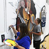 OBA art teacher, Lacye Russell and Parker Schovanec work on a mural inside the Oklahoma Bible Academy gym Wednesday, July 10, 2019. The mural is a gift from the class of 2019. (Billy Hefton / Enid News & Eagle)