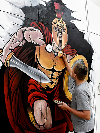 Parker Schovanec works on a mural inside the Oklahoma Bible Academy gym Wednesday, July 10, 2019. The mural is a gift from the class of 2019. (Billy Hefton / Enid News & Eagle)