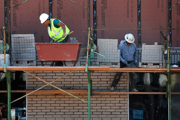Masonry workers brick the downtown hotel Thursday, July 11, 2019. (Billy Hefton / Enid News & Eagle)