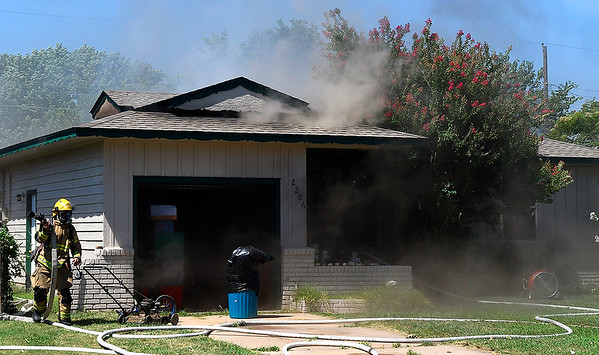 An Enid firefighter pulls hoses into place as smoke pours out of 2206 E. Ash Thursday, July 18, 2019. (Billy Hefton / Enid News & Eagle)
