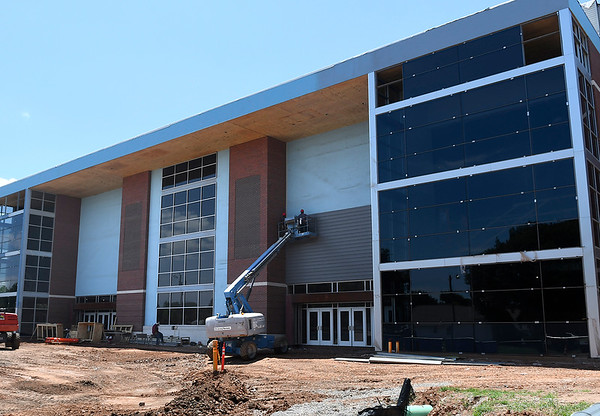 Construction workers hang siding on the new performing arts center and gym at Enid HIgh School Monday, July 8, 2019. (Billy Hefton / Enid News & Eagle)