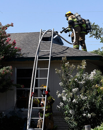 Enid firefighters spray water into the attic of 2206 E. Ash Thursday, July 18, 2019. (Billy Hefton / Enid News & Eagle)