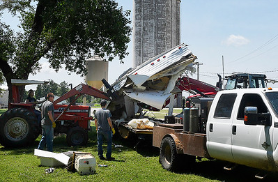 Volunteers use tractors to lift the remains of a moble home onto a trailer in Goltry after a thunderstorm moved across Alfalfa county Saturday night, July 11, 2020. (Billy Hefton / Enid News & Eagle)