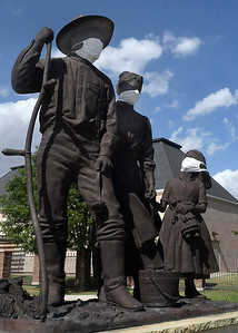 "Masks have been placed on the Harold Holden sculpture ""The Homesteaders"" at the Cherokee Strip Regional Heritage Center Wednesday, July 8, 2020. (Billy Hefton / Enid News & Eagle)"