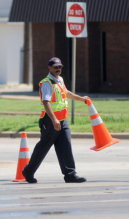 An Enid firefighter closes traffic lanes at the corner of N. Grand and E. Willow after an hydraulic fluid spill Tuesday, June 18, 2013. (Staff Photo by BONNIE VCULEK)