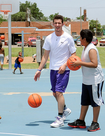 Harrison Maud visits with Jojo Huerta during a Give Me A Shot mini basketball camp at the Don Haskins Court Thursday, June 20, 2013. Give Me A Shot, a local 501-C3 begun by Maud, Eduardo Lima and Connor Choate, used donations to install 4 new hoops and distribute 25 new basketballs to Enid youth. (Staff Photo by BONNIE VCULEK)