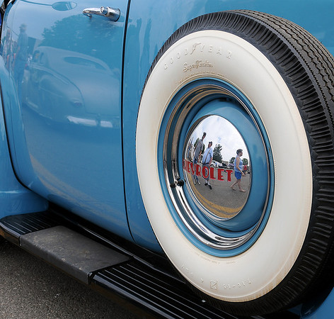 Josh Pitts' reflection appears in the hub cap on Jennifer Pitts' 1953 Chevrolet Pickup as Pitts visits with John and Ginny Tripp during the 3rd annual Van Buren Cruisin Car Show in downtown Enid Saturday, June 15,  2013. (Staff Photo by BONNIE VCULEK)