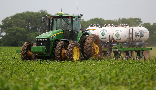 A farmer's silhouette appears inside the cab of a John Deere 8530 as he applies anhydrous ammonia to a field of corn along Cleveland Saturday, June 8, 2013. (Staff Photo by BONNIE VCULEK)