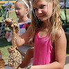 Isabelle Groendyke holds the pine cone bird feeder that she created at Enid Farmers Market Saturday, June 22, 2013. (Staff Photo by BONNIE VCULEK)