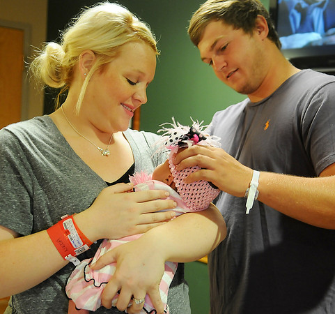 James Semrad (right) places a headband on his newborn daughter, Synthia, as his wife, Randi, holds their first-born child at Integris Bass Baptist Health Center Friday, June 14, 2013. Little Synthia, who weighed 9 lbs. 12.5 oz. at her birth on June 11, is an early Father's Day gift for James. (Staff Photo by BONNIE VCULEK)