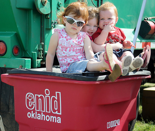 Adeline, Anna Belle and Amelia Braden hang out on a recycle bin during GreEnid at Enid Farmers Market Saturday, June 22, 2013. (Staff Photo by BONNIE VCULEK)