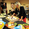 As Hank Ross (back left) watches Kristi Browne cut a birthday cake as Ross Health Care employees celebrate their 10th anniversary in Enid Wednesday, June 26, 2013. (Staff Photo by BONNIE VCULEK)