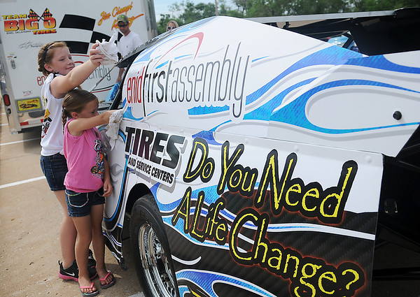 Taryn and Torie Rhodes polish the Team Big O race car for their dad, Branden Rhodes, during the 9th annual Enid First Assembly of God Dad Fest Sunday, June 16, 2013. (Staff Photo by BONNIE VCULEK)
