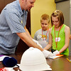 Cherokee Strip Regional Heritage Center curator, David Kennedy, helps Alexis Owens and Micah Gray to prepare an exhibit a camp at the museum Monday. (Staff Photo by BILLY HEFTON)