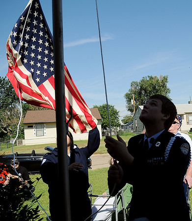 Enid High School ROTC Cadet Sr. MSgt. Zach Willig (right) raises the American flag as Cadet Major Laisa Pack during a special ceremony at The Living Center, 1409 N. 17th, Sunday, June 30, 2013. (Staff Photo by BONNIE VCULEK)