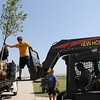 Bobby Paul, from Edmond, and Chad Hanson (from left) transfer a large tree to a New Holland fork lift as Don Smith, owner of Enid Image Design, moves new trees to a residential landscape west of the intersection of Imo Road and Willow Wednesday, June 26, 2013. (Staff Photo by BONNIE VCULEK)