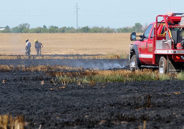 After two Enid Fire Department grass rigs become stuck in mud, firefighters extinguish the hot spots on foot during a wheat field blaze at 66th and Willow Tuesday, June 18, 2013. (Staff Photo by BONNIE VCULEK)