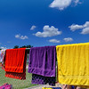 Towels hanging on the fence at Champions park splash pad make for a colorful summer afternoon scene. (Staff Photo by BILLY HEFTON)