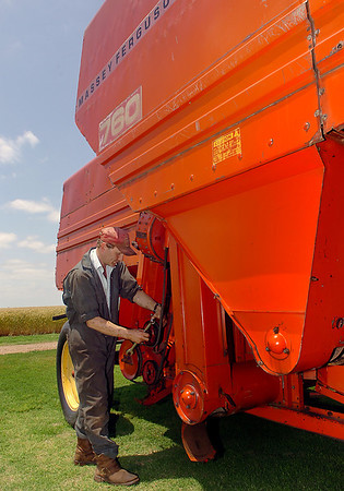 Kevin Clarke works on a 1971 Massey Ferguson Model 760 combine that he and his brother, Steven, have working to restore since mid-May. The Massey Ferguson combine was the first of 10 such combines manufactured in 1971. (Staff Photo by BILLY HEFTON)