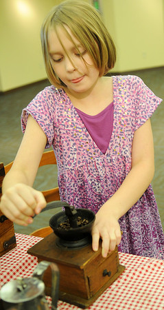 Alexis Owens demonstrates how to grind coffee beans during the Cherokee Strip Regional Heritage Center Living History Day Saturday, June 8, 2013. (Staff Photo by BONNIE VCULEK)