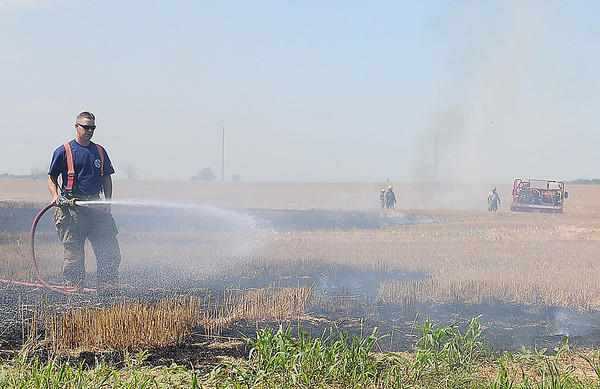 Enid firefighters extinguish a wheat field blaze at 66th and Willow Tuesday, June 18, 2013. (Staff Photo by BONNIE VCULEK)