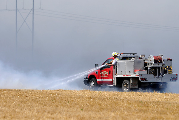 A Pioneer Skeleton Creek brush unit was among the units responding to a wheat field fire along Wheat Capital Rd. and between 72nd and 90th streets Monday. (Staff Photo by BILLY HEFTON)