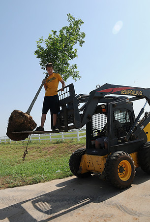 Chad Hanson (left) holds a large tree between the forks of a New Holland lift as Don Smith, owner of Enid Image Design, moves the tree on to a residential landscape west of the intersection of Imo Road and Willow Wednesday, June 26, 2013. (Staff Photo by BONNIE VCULEK)