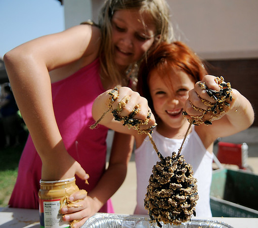 Isabelle Groendyke and Mia Lavicky create pine cone bird feeders during GreEnid at Enid Farmers Market Saturday, June 22, 2013. (Staff Photo by BONNIE VCULEK)
