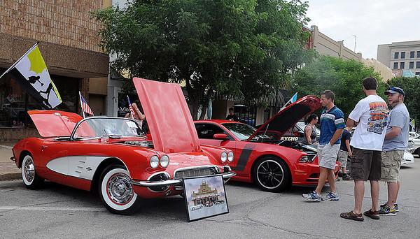 Car enthusiasts discuss their rides during the 3rd annual Van Buren Cruisin Car Show in downtown Enid Saturday, June 15, 2013. (Staff Photo by BONNIE VCULEK)