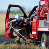 Enid firefighter, Jason Congdon, uses a shovel as he tries to dig a grass rig out of a muddy field as other firefighters battle a wheat stubble fire at 66th and Willow Tuesday, June 18, 2013. (Staff Photo by BONNIE VCULEK)