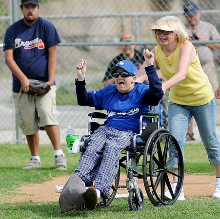 David Sawyers cheers along the first base line with his buddy, Becky Allen, after his hit in the second inning against the Braves during the final Miracle League game of the season at AMBUCS' ABC Park Saturday, June 29, 2013. (Staff Photo by BONNIE VCULEK)