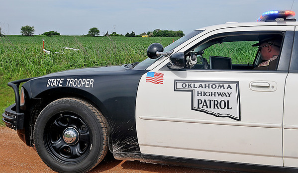 Oklahoma Highway Patrol Trooper Josh Byrd investigates the scene of an aircraft crash near Covington Thursday, June 6, 2013. Harbet Marshall, 44, of Newalla, took off from Cassody Flying Service in a 1977 Grumman Agcat G-164B (top left) and crashed approximately one and one-quarter miles south of the business. Miraculously, Marshall walked away from the crash with only a small cut on a finger. Oklahoma Highway Patrol and Covington Fire Department responded to the location. (Staff Photo by BONNIE VCULEK)