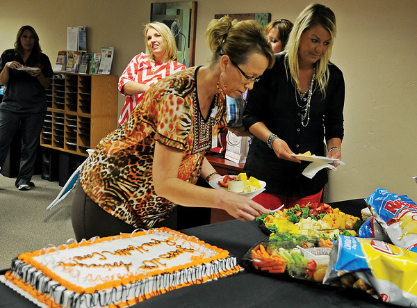 Barbara Honigsberg and Kristi Browne (front, from left) select healthy snacks as Ross Health Care employees celebrate their 10th anniversary at 427 E. Cherokee Wednesday, June 26, 2013. Since the business opened in Enid, they have assisted nearly 10,000 clients. (Staff Photo by BONNIE VCULEK)