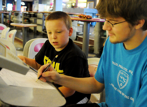 R.J. Hooper (left), an 11-year-old sixth-grade student at Emerson Middle School, and Kelsy Peck, a 16-year-old, eleventh-grade student at Enid High School check their score card during the Oakwood Bowl youth scholarship bowling Tuesday, June 11, 2013. (Staff Photo by BONNIE VCULEK)