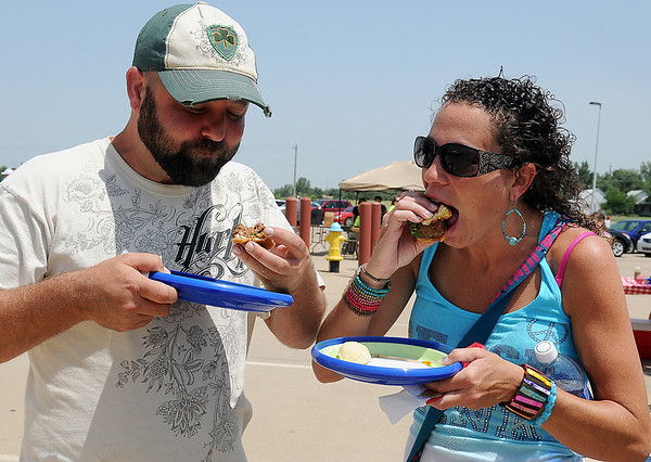 Shane McGee and Chandra Hildabrand enjoy Crappy's gourmet burger during Make-A-Burger for Make-A-Wish at the Chisholm Trail Expo Center Saturday, June 22, 2013. (Staff Photo by BONNIE VCULEK)