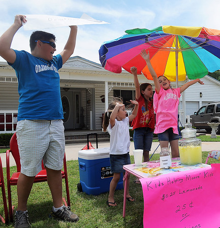 Cooper Wieden, Lakyn Starr Young, Madelyn Sutton and Taylor Wieden (from left) cheer as they wave down cars near Young's lemonade stand Saturday, June 8, 2013. Young, who worries about children who lost their dolls and other toys during the Moore tornado, has been selling lemonade since Friday. By 1:30 p.m. Saturday, she had nearly $500 to buy new toys for the children in Moore. (Staff Photo by BONNIE VCULEK)