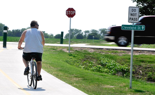 A cyclist checks traffic as he approaches Cleveland St. while riding the Enid Trail system. (Staff Photo by BILLY HEFTON)