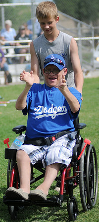 Dusty Decker celebrates his single as his buddy pushes him to first base during the Dodgers' final game of the 2013 Miracle League season Saturday, June 29, 2013. (Staff Photo by BONNIE VCULEK)