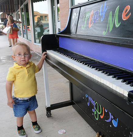 Levi Ford pauses next to a piano during First Friday activities June 7, 2013. (Staff Photo by BONNIE VCULEK)